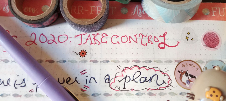 """My bullet journal with the words """"2020: Take control"""" surrounded by colourful washi tape and stickers. The word """"plan"""" is cloud-circled."""